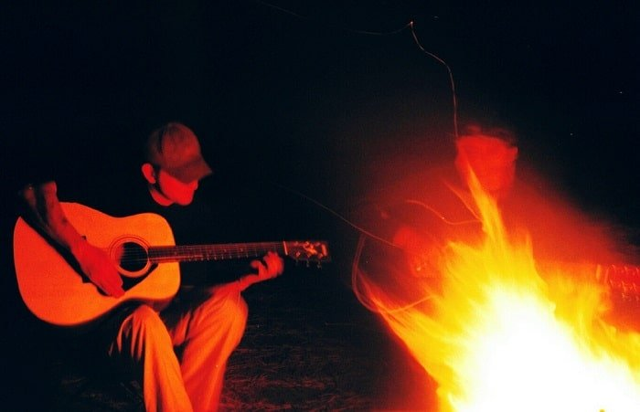 Guy playing guitar in front fire